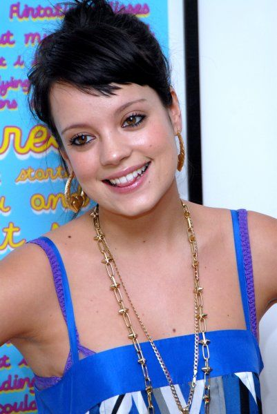 Gobby chart-topper Lily Allen poses for photographers as she signs copies of artwork created from the lyrics of one of her songs